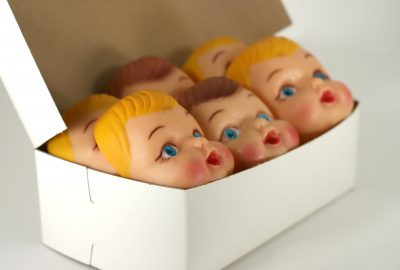 A close up of plastic doll faces in a box ready for assembly